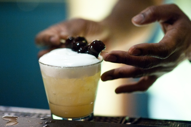 Barman rests cherries on foam of whiskey sour